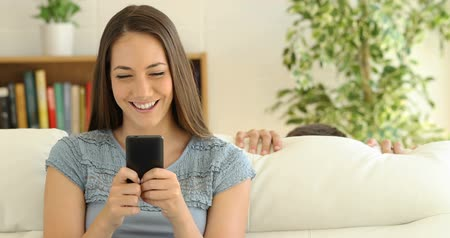 gives you : Cheater woman dating on a smart phone and boyfriend is spying on a sofa at home Stock Footage