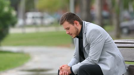 complaints : Side view portrait of a worried businessman sitting on a bench in a park