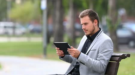 complaints : Businessman reads bad online news in a tablet and complaints sitting on a bench in a park Stock Footage