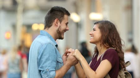 seducing : Side view of a happy couple holding flirting hands in the street Stock Footage