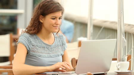 grants : Excited woman reading good news in a laptop at a coffee shop Stock Footage