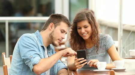 gives : Happy couple talking about smart phone content in a coffee shop in a rainy day