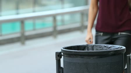 desfocado : Close up of a girl throwing a paper into bin Stock Footage