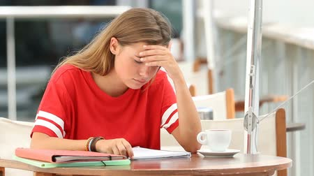 estudioso : Frustrated student studying reading of a difficult lesson in a coffee shop
