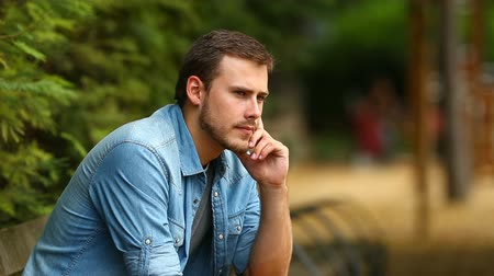 hand on chin : Portrait of a serious pensive guy sitting on a bench in a park