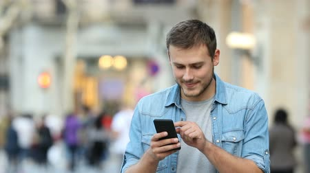 average : Front view of a man walking and using a smart phone in the street Stock Footage