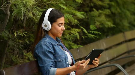 wearing earphones : Happy woman wearing headphones watching online videos in a tablet sitting on a bench in a park Stock Footage