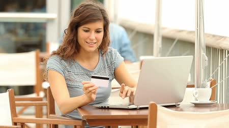 financiamento : Happy woman shopping with a laptop and paying with credit card in a coffee shop