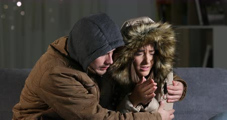 crashed : Cold home with an angry couple hugely clothed hugging on a sofa in the living room at home in the night