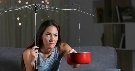 karartmak : Woman suffering water leaks at home with a broken umbrella. Bad insurance concept