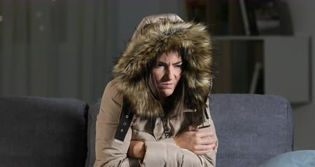 mrazivý : Angry woman warmly clothed in a cold home sitting on a couch in the night