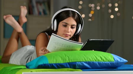 master's degree : Teen e-learning comparing to tablet and notebook notes lying on a bed in the night at home