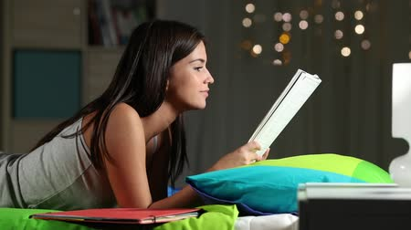 master's degree : Side view portrait of a teenage girl reading a notebook on a bed at home in the night