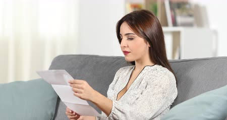 verificar : Surprised woman reading a letter sitting on a couch at home
