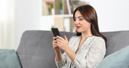 átlagos : Happy woman chatting with a smart phone sitting on a couch at home