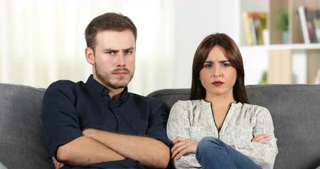 dispute : Front view of an angry couple looking at camera sitting on couch at home