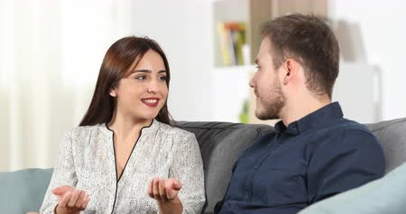 gives : Couple sitting talking on couch at home