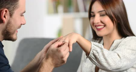 propor : Happy man putting engagement ring on the hand of his girlfriend at home Vídeos