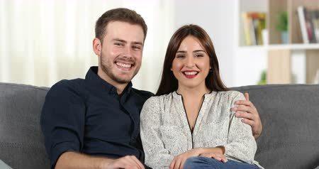 esteem : Happy couple laughing looking at camera sitting on couch at home