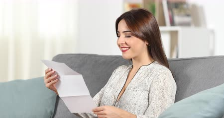 открытка : Happy woman reading a letter sitting on a couch at home Стоковые видеозаписи