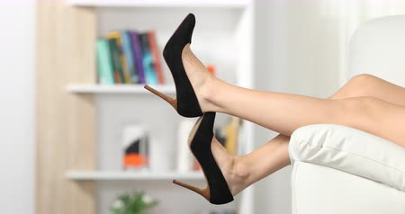 interior : Close up of woman legs sitting on a couch and resting taking off shoes at home