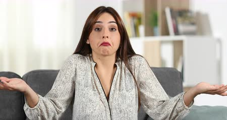 doubt : Front view of a doubtful woman shrugging shoulders to camera sitting on a couch in the living room at home Stock Footage
