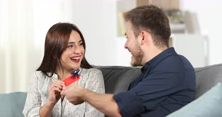 давать : Happy man gives a gift to his girlfriend on a couch at home