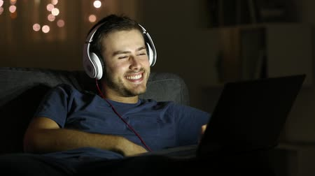 banda larga : Happy man watching videos on a laptop sitting on a couch in the living room in the night at home