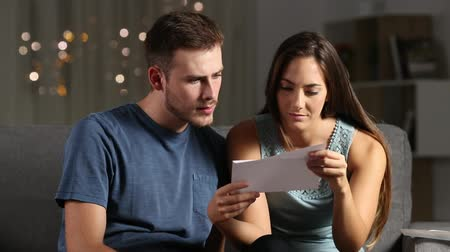 cytat : Sad couple reading bad news in a letter in the night at home