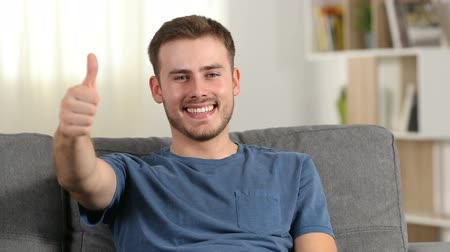 acceptance : Front view of a happy man gesturing thumbs up on a couch at home