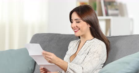 refund : Happy woman reading a letter sitting on a couch in the living room at home Stock Footage