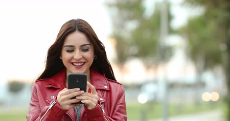 sending : Front view of a happy woman messaging with a smart phone in a park