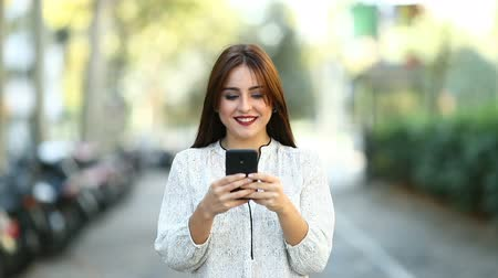 looking towards : Front view of a happy woman walking and using a smart phone in the street