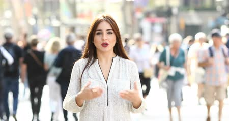 looking towards : Front view of a woman talking and walking towards camera in the street