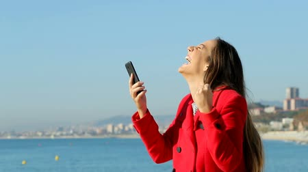 grants : Side view portrait of an excited woman using a smart phone on the beach in winter