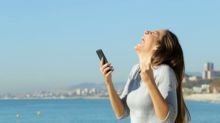 alku : Profile of an excited woman using a smart phone finding online on the beach. Slow motion