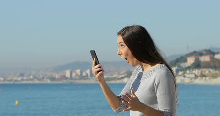 heyecan verici : Side view portrait of a surprised woman finding exciting content on a smart phone on the beach Stok Video