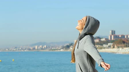atitude : Side view portrait of a happy teen breathing fresh air on the beach Stock Footage