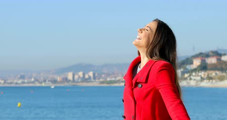 atitude : Side view portrait of a happy woman in red breathing deep fresh air in winter on the beach