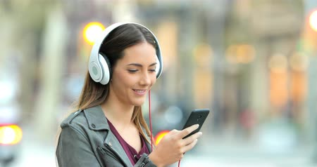 песня : Smiley girl wearing headphones listening to music from a smart phone in the street Стоковые видеозаписи