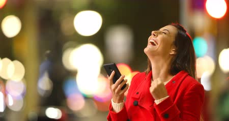 tebliğ : Excited woman checking good news on a smart phone in the night in the street Stok Video