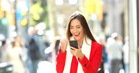 açık artırma : Front view of an excited woman walking towards camera receiving good news online on a smart phone in the street in winter Stok Video