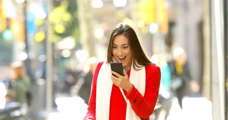 barganha : Front view portrait of a shocked woman walking towards camera reading online news on a smart phone in the street