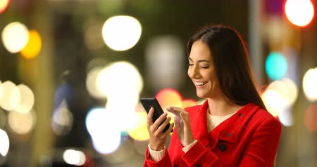 average : Happy woman browsing smart phone content in a winter night in the street