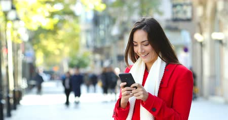 по электронной почте : Happy woman wearing a red jacket texting on smart phone in winter in the street