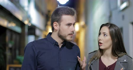 dispute : Front view of an angry couple arguing in the night walking towards camera in the street