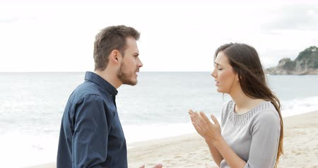 elválasztott : Angry couple breaking up on the beach. Boyfriend, leaves his sad girlfriend