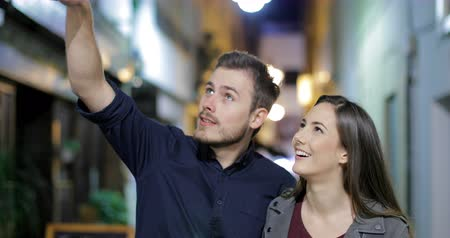 gives you : Front view of a happy couple walking towards camera sightseeing in the night in the street Stock Footage