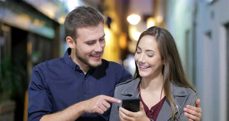 family watching tv : Front view of a happy couple walking with a smart phone in the night in the street of an old town Stock Footage