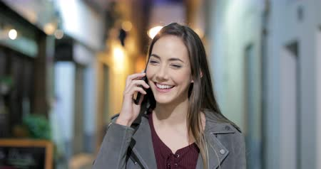 talep : Front view of a happy woman talking on phone walking towards camera in the night in the street